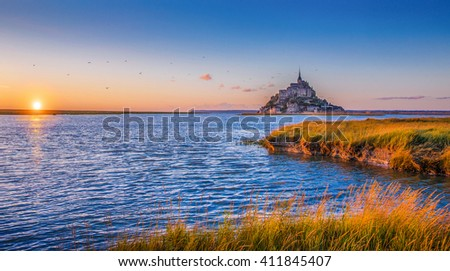 Panoramic view of famous historic Le Mont Saint Michel tidal island in beautiful golden evening light at sunset in summer, Normandy, northern France - stock photo