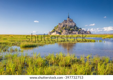 Panoramic view of famous historic Le Mont Saint-Michel tidal island on a sunny day with blue sky and clouds in summer, Normandy, northern France - stock photo