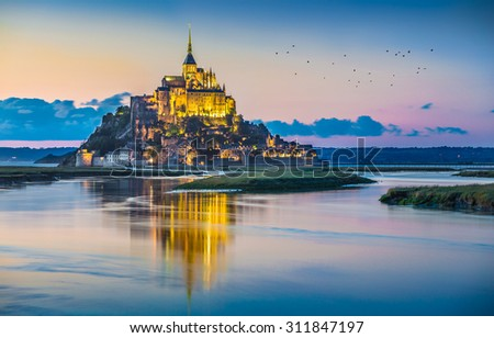 Panoramic view of famous Le Mont Saint-Michel tidal island in beautiful twilight during blue hour at dusk, Normandy, northern France - stock photo