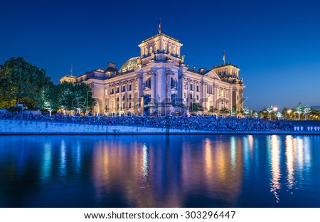 Panoramic view of famous Reichstag building, seat of the German Parliament (Deutscher Bundestag), with Spree river in twilight during blue hour at dusk, Berlin Mitte, Germany - stock photo