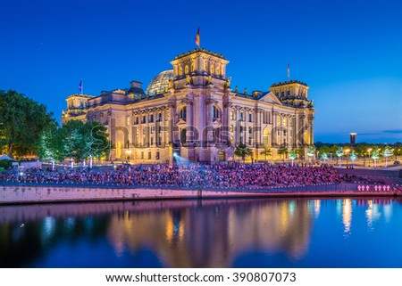 Panoramic view of famous Reichstag building, seat of the German Parliament (Deutscher Bundestag), with Spree river in twilight during blue hour at dusk, Berlin Mitte district, Berlin, Germany - stock photo
