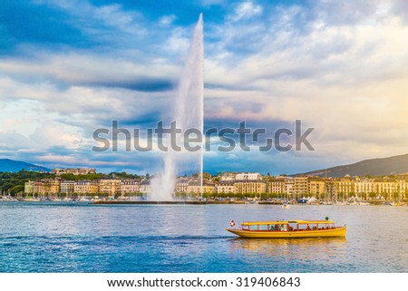 Panoramic view of Geneva skyline with famous Jet d'Eau fountain and traditional boat at harbor district in beautiful evening light at sunset, Canton of Geneva, Switzerland - stock photo