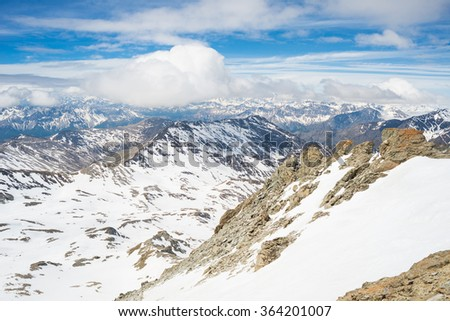 Panoramic view of high mountain peaks and snowcapped ridges at high altitude in the italian french alpine arc. Scenic sky and clouds covering the valley below. - stock photo