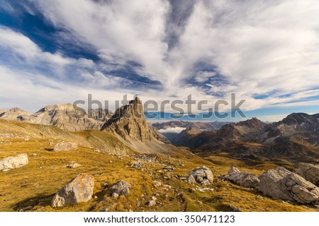 Panoramic view of high mountain range in a colorful autumn with green yellow meadows and rocky mountain peaks. Wide angle shot in the Italian French Alps. - stock photo