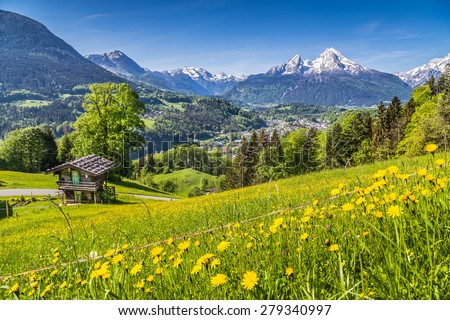 Panoramic view of idyllic mountain landscape in the Alps with fresh green mountain pastures with flowers and old traditional mountain lodge in springtime - stock photo