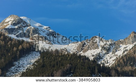 Panoramic view of idyllic winter wonderland with mountain tops in the Alps on a sunny day with blue sky, Hinterstoder  skiing resort, Austria - stock photo