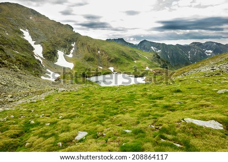 Panoramic view of Lake Capra from Fagaras mountains - stock photo