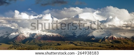 "Panoramic view of Lenin Peak from Alay range - Kyrgyz Pamir Mountains - Kyrgyzstan and Tajikistan border- Central Asia ""Roof of the World""  - stock photo"