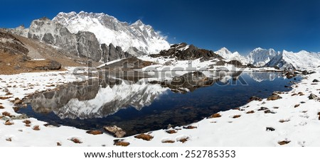 Panoramic view of Lhotse and Nuptse south rock face and Makalu mirroring in small lake on the way to Everest base camp - Sagarmatha national park - Nepal - stock photo