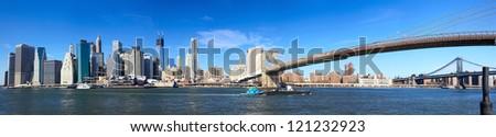Panoramic view of Manhattan skyline and Brooklyn Bridge in New York City - stock photo