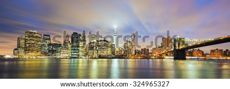 Panoramic view of New York City Manhattan midtown at dusk with skyscrapers illuminated over east river - stock photo