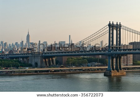 Panoramic view of New York city with the Manhattan Bridge crossing the East River in the foreground at sunrise or sunset - stock photo