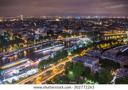 Panoramic view of Paris city from Eiffel tower in moonlit night with light traced from ships moving along Seine river - stock photo
