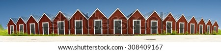 Panoramic view of row of traditional red wooden boathouses on blue sky in summer in small Swedish town - stock photo