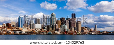 Panoramic view of Seattle waterfront and downtown buildings on a bright day with sun and clouds - stock photo