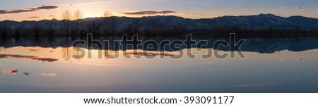 Panoramic view of Snowed Peak Mountains Reflecting on a large Lake - stock photo