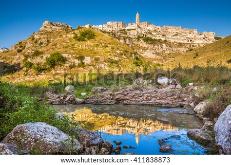 Panoramic view of the ancient town of Matera (Sassi di Matera), European Capital of Culture 2019, in beautiful golden morning light with blue sky reflecting in lake, Basilicata, southern Italy - stock photo