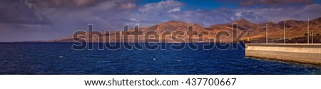 Panoramic view of the coastline of Lanzarote as seen from the harbour in Puerto del Carmen in Lanzarote,  Canary Islands, Spain - stock photo