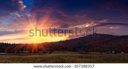 Panoramic view of the dramatic sunset in the autumn mountains. Colorful forest on the slopes. Old farm and pasture for grazing horses. - stock photo