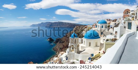 Panoramic view of the Oia village under puffy clouds, Santorini island, Greece - stock photo