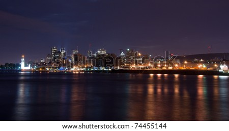 Panoramic View of the port of Montreal with office buildings in the background view of St-Lawrence River at night. - stock photo