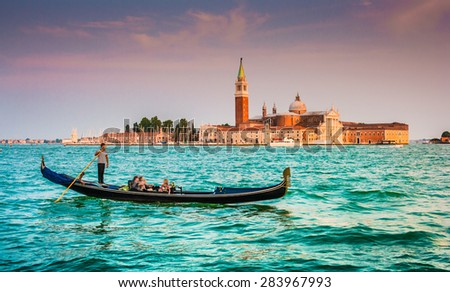 Panoramic view of traditional Gondola on Canal Grande with San Giorgio Maggiore church in the background in beautiful evening light at sunset, San Marco, Venice, Italy - stock photo