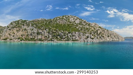 panoramic view of turquoise lagoon and rocky island against blue sky on sunny day in Aegean sea on sighseeing boat trip, Turkey - stock photo