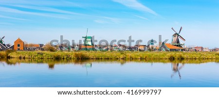 Panoramic view of windmill in Zaanse Schans, traditional village in Holland, reflection in lake, blue sky, copy space - stock photo