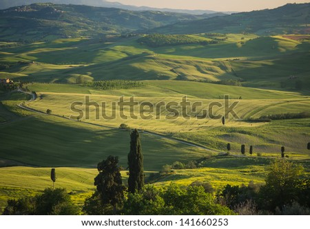 Panoramic view on green fields in Tuscan landscape with shadows falling over the slopes - stock photo