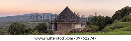 Panoramic view on lodge hotel bungalows against sunrise glowing over mountain background at dawn. Ngorongoro, Great Rift Valley, Tanzania, East Africa.  - stock photo