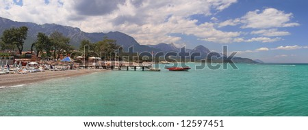 Panoramic view on public beach, Mediterranean Sea and mountains in popular touristic resort Kemer (Antalya), Turkey. - stock photo
