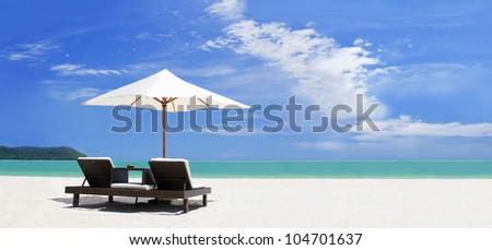 panoramic view ow the tropical beach with umbrella and two beds - stock photo