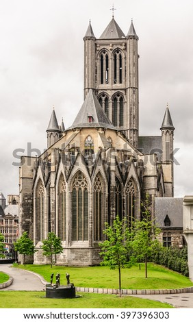 Panoramic view to the square and park near the of St. Bavo Cathedral and St. Nicholas church (Sint-Niklaaskerk) under the dark sky with clouds in the historic part of Ghent, Belgium - stock photo