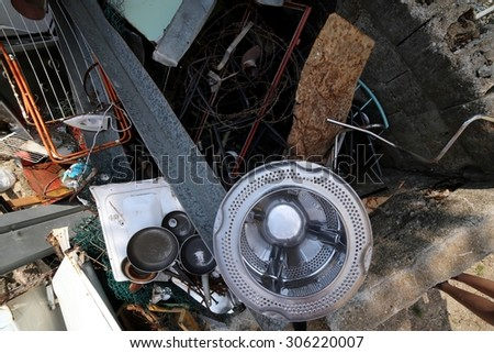 pans and washing machine basket and rusty iron ore dump in special waste landfill - stock photo