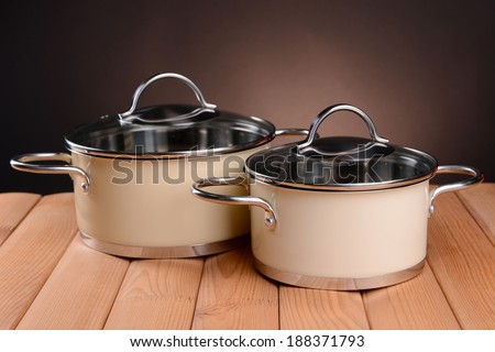 Pans on table on brown background - stock photo