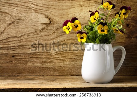 Pansy flower on wooden background - stock photo