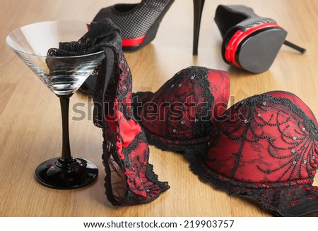 Panties in a martini glass on the background of  shoes and  bra, can be used as a background - stock photo