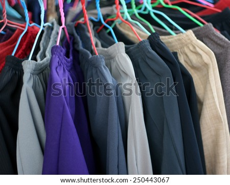pants hanging on a rack market for sale - stock photo