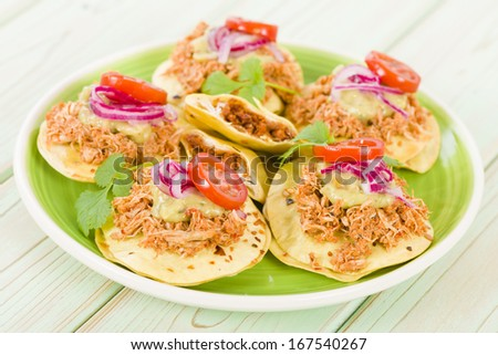 Panuchos - Mexican corn tortillas filled with refried beans and topped with shredded chicken, guacamole, pickled red onions and tomato. - stock photo