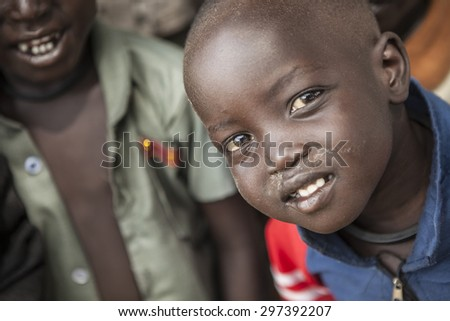 PANWEL, SOUTH SUDAN: NOVEMBER 2, 2013: Portrait of a curious little boy of the Dinka tribe in a rural area of South Sudan - stock photo
