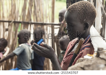 PANWELL, SOUTH SUDAN-NOVEMBER 2, 2013: An unidentified child prays in an outdoor church in South Sudan - stock photo