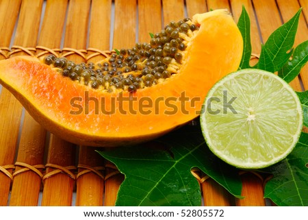 papaya and lime on bamboo - stock photo