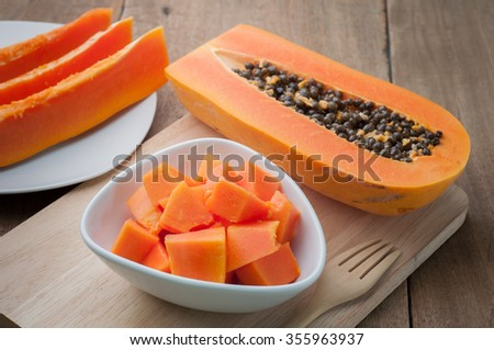 Papaya orange fresh on white dish  and papaya slice put on the wooden floor. - stock photo