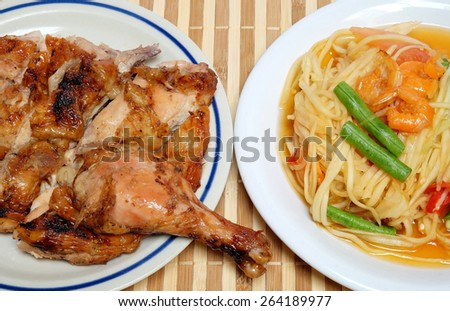 "Papaya spicy salad and Grilled Chicken or what we called ""Somtum"" and ""Gaiyang"" in Thai, Famous Thai food and yummy authentic local thai food - stock photo"