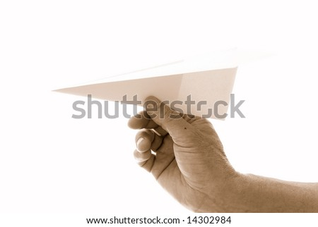 Paper aircraft is launched from hand. - stock photo