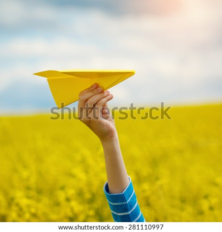 Paper airplane in children hands on yellow background and blue sky in coudy day - stock photo