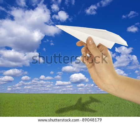 Paper airplane made in flight against a background of beautiful landscape - stock photo