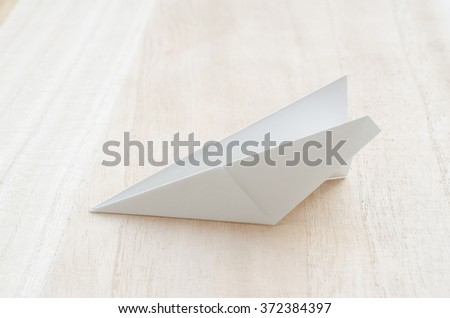 Paper airplane on wooden table - stock photo