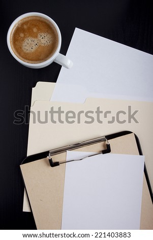 Paper and cup of coffee on the office table. - stock photo