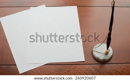 Paper and vintage pen on wooden desk - stock photo